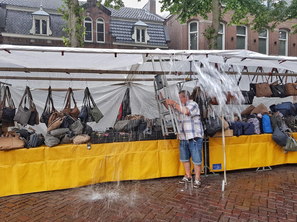 Heel andere problemen in augustus 2018 op de weekmarkt van Oisterwijk: koopman treft met keukentrapje maatregelen na stortbui.