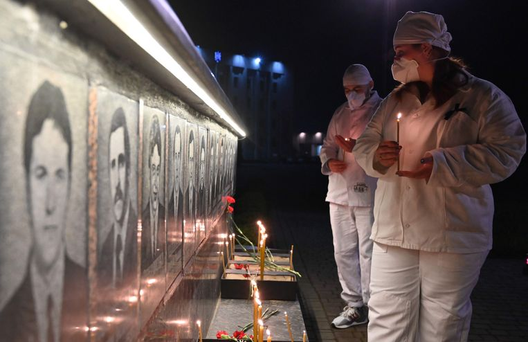 Werknemers van de kerncentrale van Tsjernobyl steken kaarsen aan bij een gedenkteken voor de slachtoffers van Tsjernobyl in Slavoetytsj, een Oekraïense stad 50 kilometer ten noorden van de centrale.