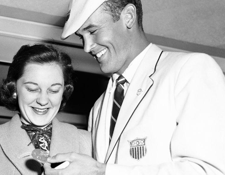 Bobby Joe Morrow toont een van zijn drie gewonnen medailles aan zijn vrouw, Joann, na de Olympische Spelen in Melbourne. Beeld AP