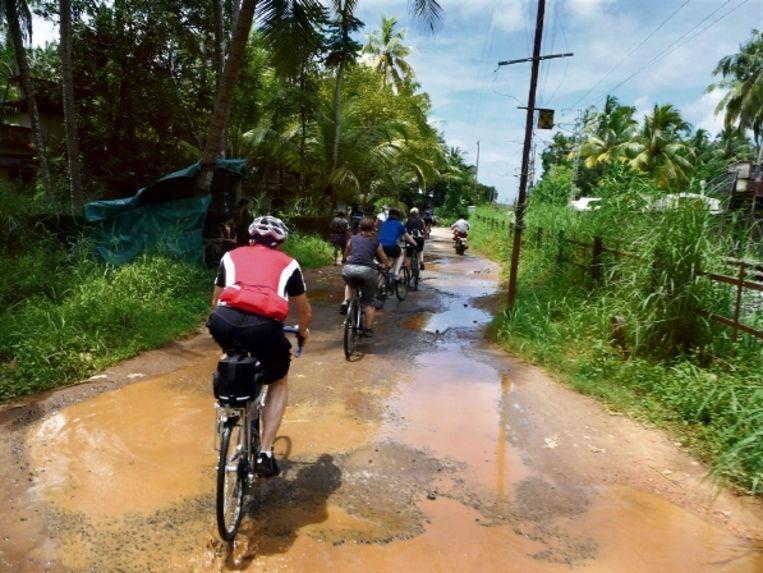Boven: de fietsen worden in een bootje geladen. Onder: hand op de rem en zeker ook op je bel. (FOTO'S MATT BASTABLE) Beeld
