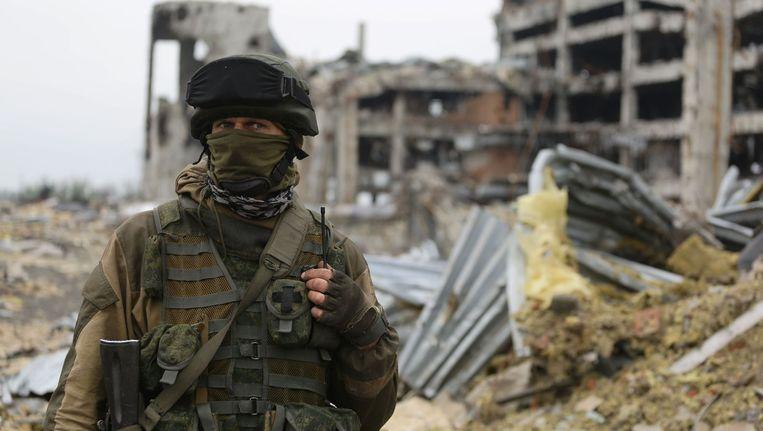 Een pro-Russische separatist voor het verwoeste vliegveld in Donetsk. Beeld afp