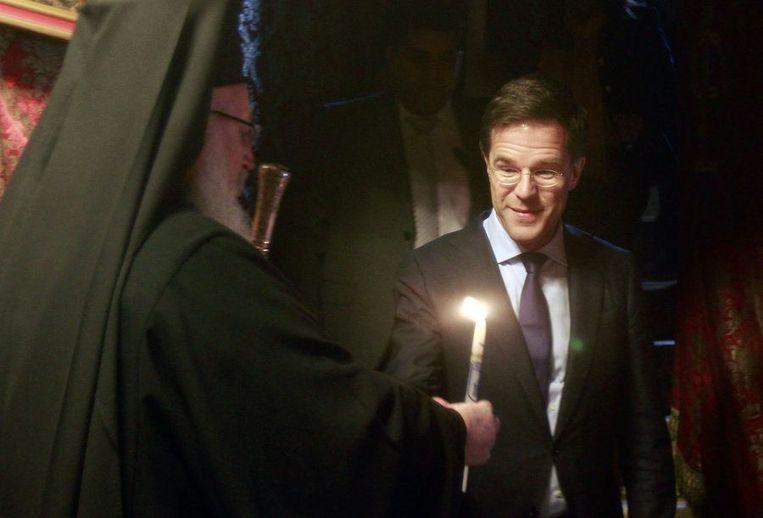 Premier Mark Rutte ontvangt in de Geboortekerk van Bethlehem een kaars uit handen van een orthodoxe priester. Beeld reuters