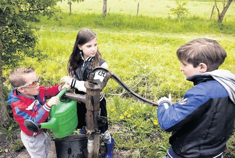 Timo, Laura en Jens Nieuwenhuize halen water voor hun moestuin. Beeld Rob Huibers