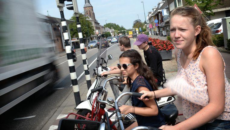 Fietsers en een scooter wachten in Aalst op groen licht voor ze de drukke verkeersweg kunnen oversteken. Beeld Marcel van den Bergh/de Volkskrant