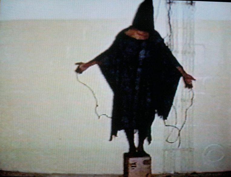 Een van de Iraakse gevangen die door de Amerikanen soldaten op een doos moest staan terwijl aan zijn handen stroomkabels werden bevestigd Beeld epa