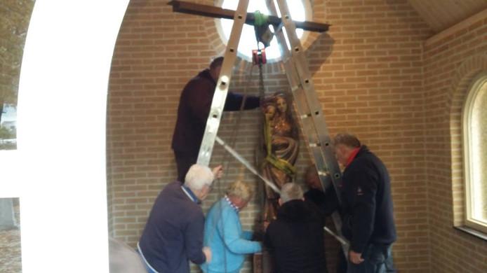 Het beeld van Maria wordt op een voetstuk geplaatst.