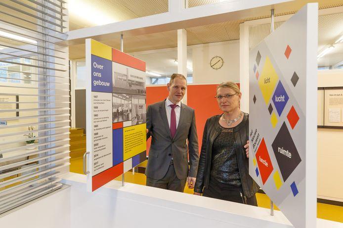 Algemeen directeur Alfred Bolks samen met projectontwikkelaar Frida Hoekman met informatieborden over het gebouw in de entreehal. De borden maken deel uit van het 'Rietveldmuseum' in het pand.