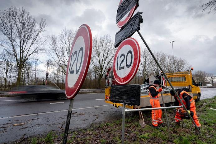 Pim Visser (rechts) en Nick de Vries plaatsen nieuwe borden langs de A59 bij Den Bosch. De oude 120 km borden worden in de middag verwijderd.