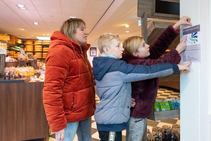 Petra van de Ven (L) samen met haar kinderen Darren (12) en Hailey (10) hangen flyers op in Terheijden voor het initiatief 'Ik help mijn buurt'.