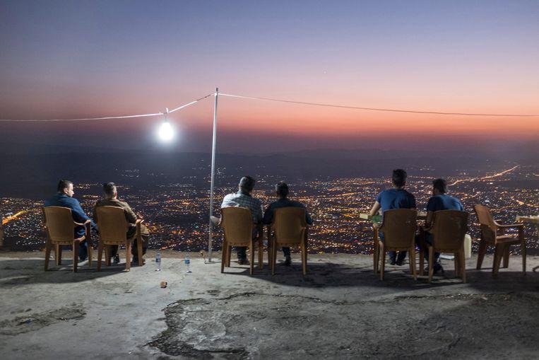 In Irak kijken mannen bij het vallen van de avond vanaf de berg Azmir uit over Soeleimania. Boven op de berg is een plek waar de oorlog ver weg lijkt. Beeld Hollandse Hoogte / Redux Pictures