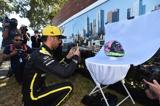 Daniel Ricciardo maakt een fotootje van een spandoek met een foto van Melbourne.