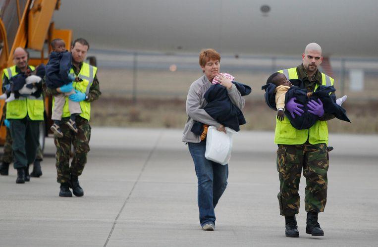 Adoptiekinderen uit Haiti worden in 2010 na aankomst op vliegbasis Eindhoven weggeleid van het vliegtuig.  In totaal 92 weeskinderen werden opgevangen door Nederlandse adoptieouders in een terminal van de luchthaven. Beeld ANP