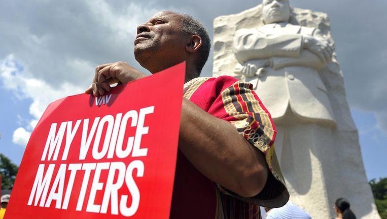 Een man met een affiche bij het monument van Martin Luther King in Washington DC. Beeld afp