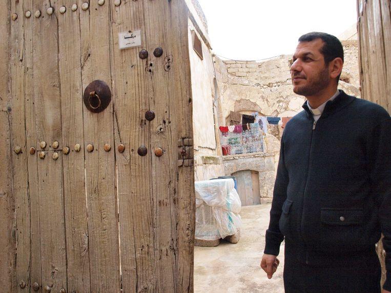 Vader Araam bij een oude deur die hij gered heeft en die nu toegang geeft tot een museumpje over het recente verleden van Al Qosh. Beeld Judit Neurink