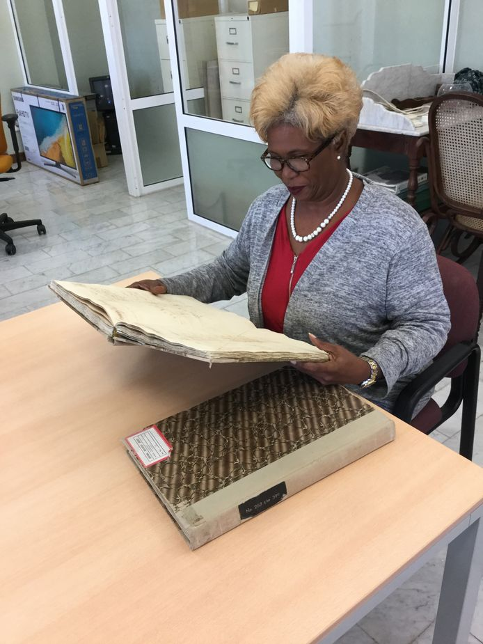 Modianne Cathalina, archivaris van het Nationaal Archief Curaçao, met twee fysieke registers.