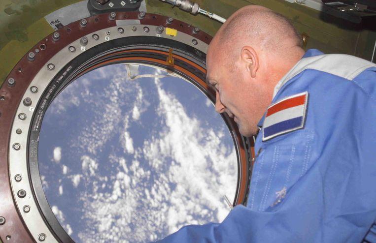 ESA-astronaut Andre Kuipers kijkt, in april 2004, uit een raam van het internationale ruimtestation ISS. Beeld null