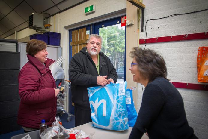 Frans Princen komt met zijn vriendin Wilma van Hofwegen zijn voedselpakket ophalen bij Willeke Peters (rechts).