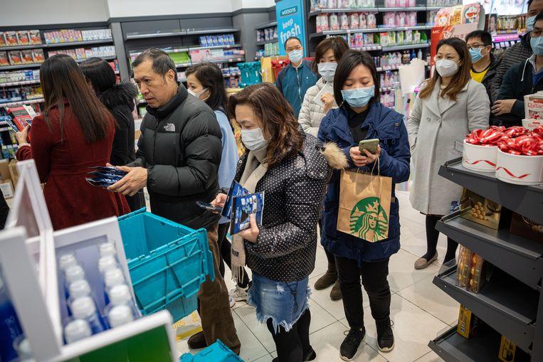 Een lange rij in een drogist in Hongkong om onder andere gezichtsmaskers aan te schaffen. Beeld EPA