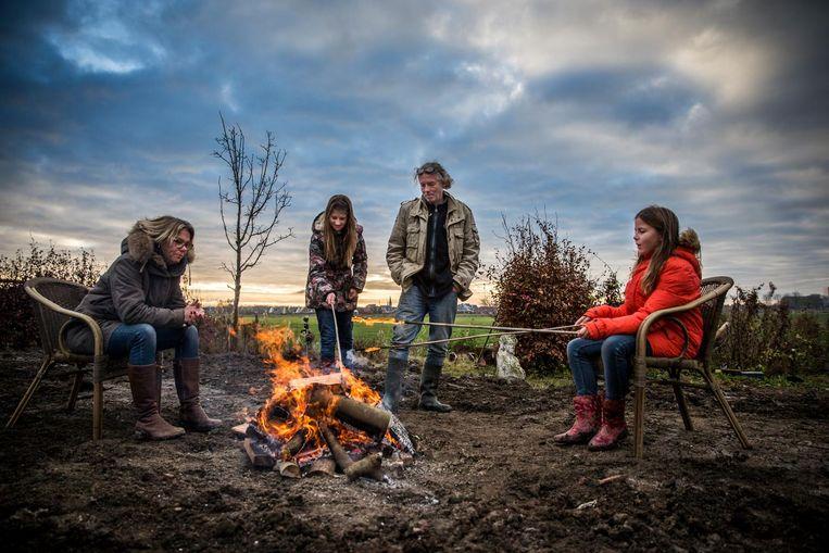 Annemarie Heite, Albert Ubels en hun dochters Annemijn en Zara op de kale vlakte, waar eens hun boerderij stond. Beeld Piet Hein van der Hoek