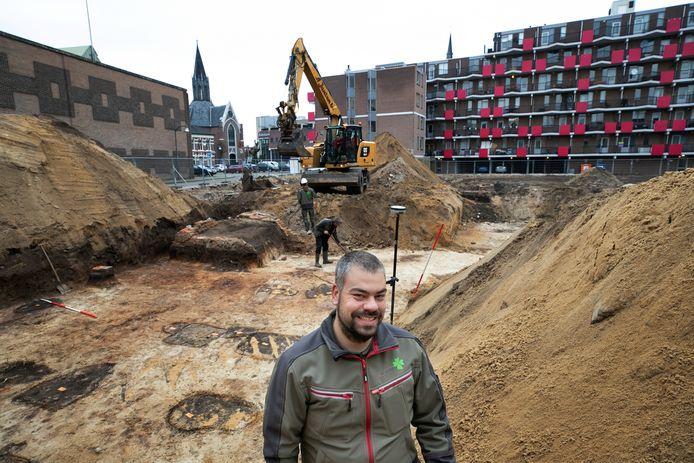 Ton Wolf bij de opgravingen aan het Beugelsplein waar gevonden paalresten lijken te wijzen op bewoning in de twaalfe eeuw toen Helmond nog stad moest worden.