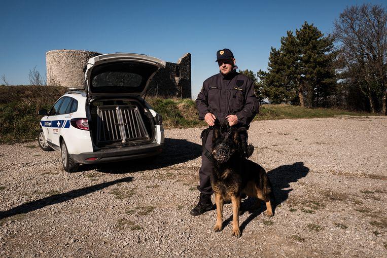 Een Sloveense grenswacht met een herdershond. Sinds afgelopen zomer heeft de plaatselijke politie hulp van het leger.  Beeld Nicola Zolin