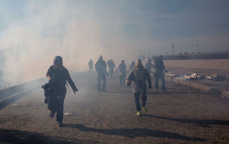 Migranten rennen weg van traangas dat is afgevuurd door Amerikaanse grenspolitie. 25 november 2018. Beeld AP