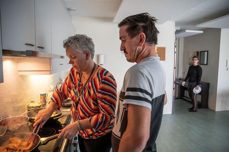 Bewoners van de Ingelandhof van Philadelphia (woonlocatie voor mensen met een verstandelijke beperking) helpen mee met het koken.  Per verdieping wordt gezamenlijk een menu gekozen, bereid en gegeten. Op de foto begeleidster Janine. Beeld Harry Cock