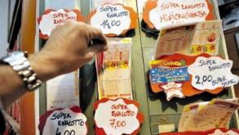 Een inwoner van Pisa pakt een formulier van de Superena-lotto. (FOTO EPA) Beeld