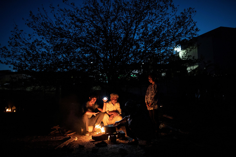 Een Afghaanse familie kookt op een vuurtje.