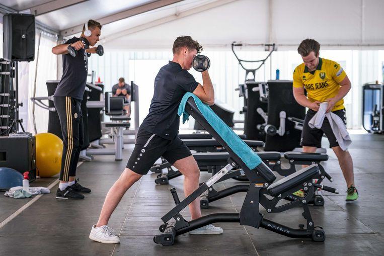 Sporters maken gebruik van de fitness apparatuur in een tent bij een sportcentrum Hoorn.  Beeld ANP