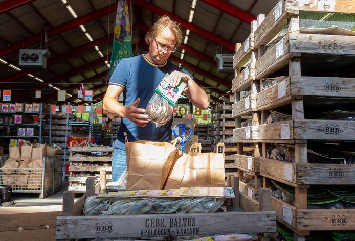 Dennis Dral maakt pakketten met bloembollen in het magazijn van Baltus Bloembollen in Vaassen. Door de coronacrisis ligt de opslag bomvol. In plaats van de bollen te laten vergaan, worden ze uitdeeld aan medewerkers van andere bedrijven en zorginstellingen in de gemeente Epe.