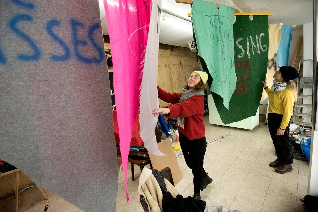 Laura de Vogel, Arnhem en Rosalie van Oorschot bekijken de vaandels in Circa Dit.