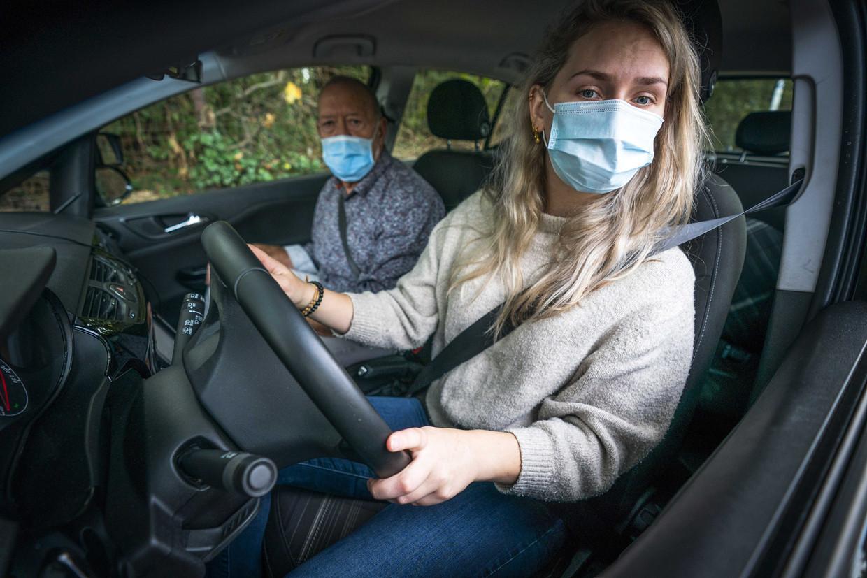 Een rijinstructeur en een leerling dragen beide een mondkapje.  Beeld ANP