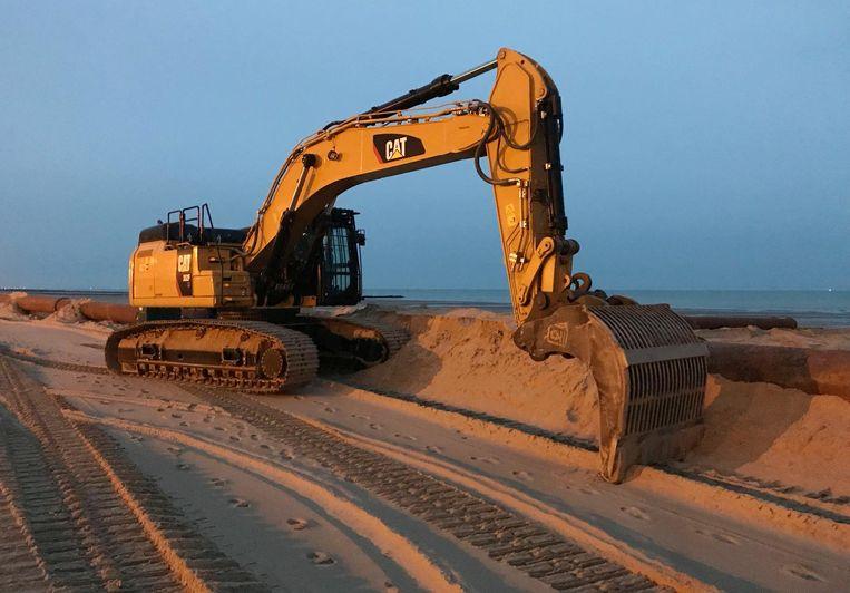 Een kraan nivelleert het aangevoerde zand.