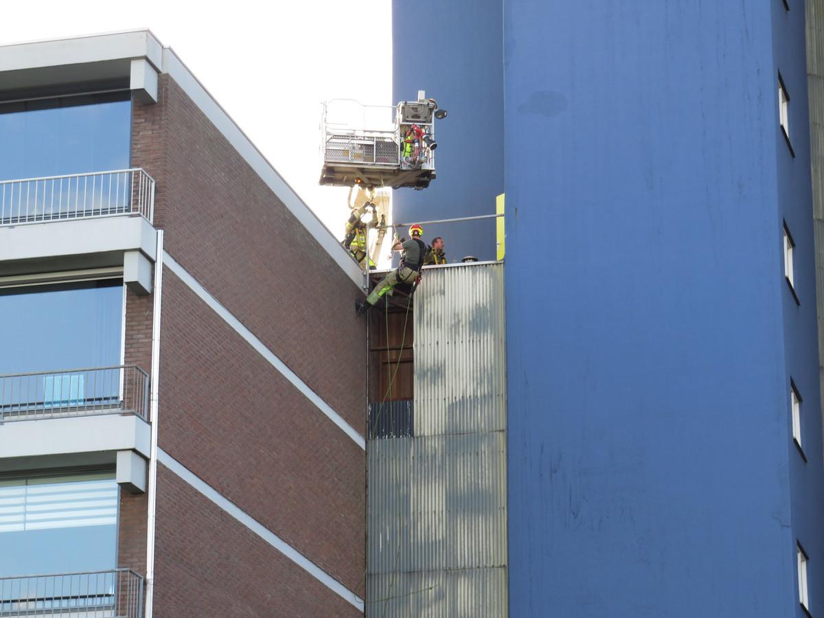Een brandweer hangt onder een hoogwerker om de losse gevelplaten te bereiken. en te verwijderen.