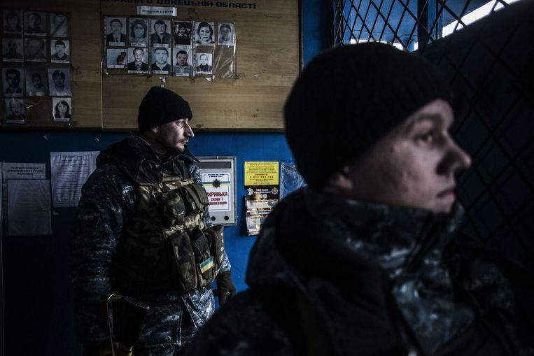 Regeringssoldaten zoeken dekking in een politiebureau in Debaltseve, na beschietingen door rebellen. Beeld afp