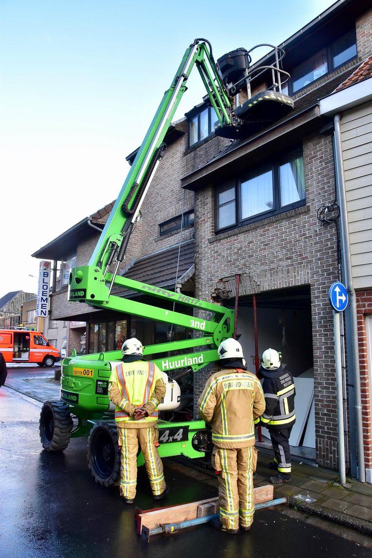 De arm van de hoogtewerker beschadigde de muur boven de garage. De brandweer moest de gevel stutten.