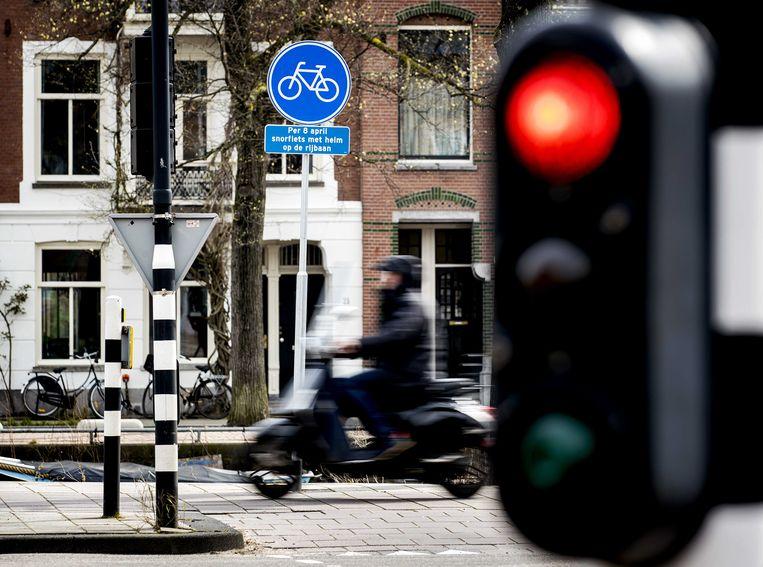 Verkeersborden in Amsterdam informeren snorfietsers voor de naderende veranderingen op fietspaden. Beeld ANP