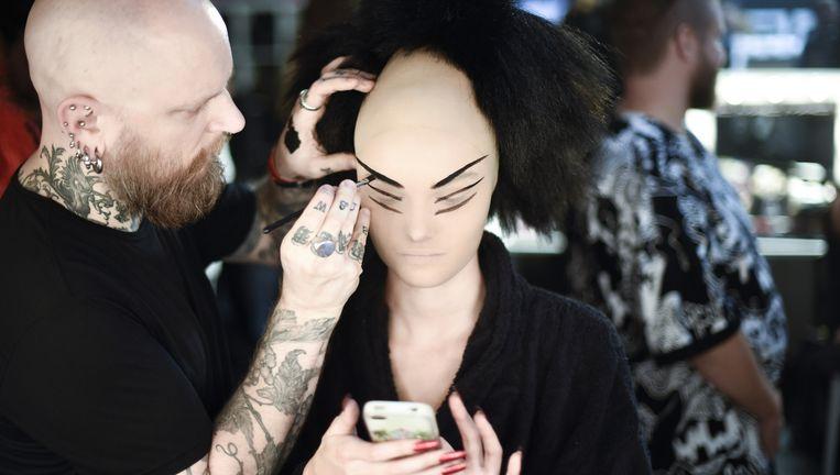 Visagist aan het werk met make-up van MAC voor een modeshow. Beeld GORUNWAY