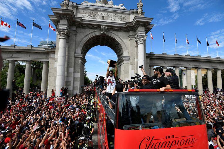 Raptors-speler Kyle Lowry toont fans de NBA-trofee tijdens een rondrit door Toronto. Beeld Reuters