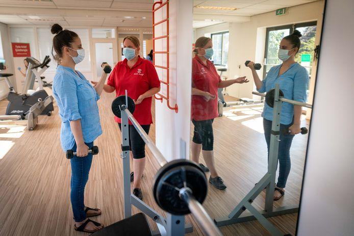 Selda Yilmaz oefent, onder toeziend ook van Annika Kulcke van Fysio-Actief, met gewichten.