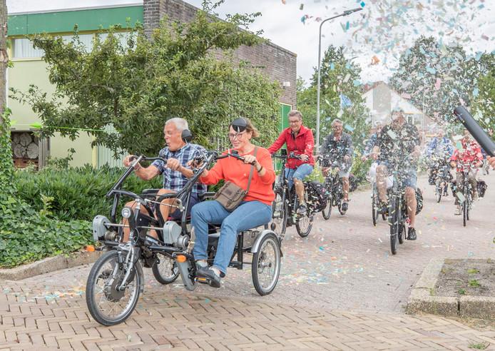 Jo de Roo (links op duo fiets) en Keetie van Oosten-Hage openen de Fietstocht door een wolk een wolk van confetti.
