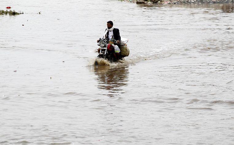 Een man rijdt door een overstroomde straat in Sanaa, 25 juli 2017. Beeld epa