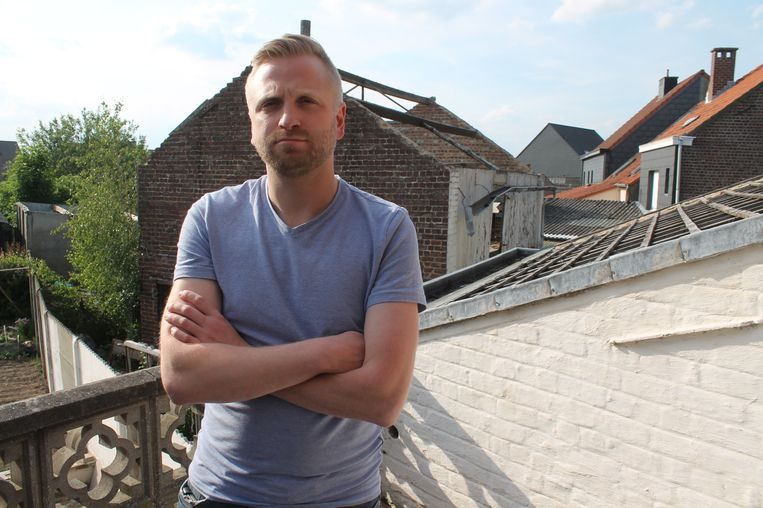 Buurtbewoner Dieter Timmermans met het verloederde huis in de achtergrond.
