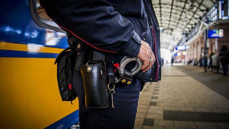 Handboeien bij een service- en veiligheidsmedewerker van de Nederlandse Spoorwegen op het station Beeld anp