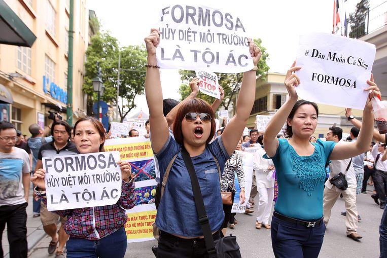 Vietnamese demonstranten houden protestborden omhoog in Hanoi over de giframp die staalfabriek Formosa veroorzaakte in 2016. Beeld EPA