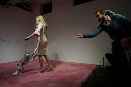 Le mannequin passe l'aspirateur sur son carré de moquette, que les visiteurs lui lancent des miettes ou non.