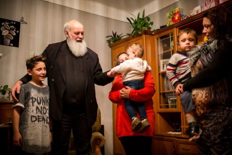 Predikant Gábor Iványi doopt een meisje en een jongen tijdens zijn bezoek aan een gezin in het Roma-dorp Gyöngyöspata. Beeld Julius Schrank
