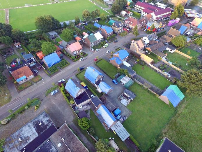 Een luchtfoto van Luyksgestel laat zien hoe groot de schade na de hagelstorm is. Vrijwel alle daken zitten vol gaten en zijn daarom afgedekt met blauwe en oranje zeilen.