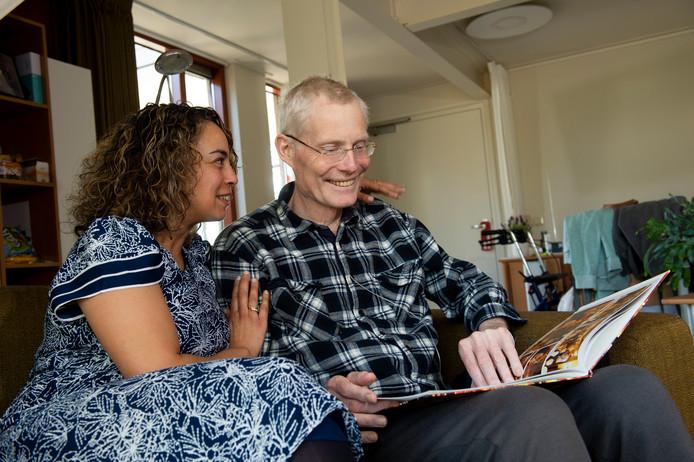 Hospice Apeldoorn houdt open huis. Op de foto Lex Brons en zijn vriendin Samira. Ze belijken het fotoalbum van zijn afscheidsfeest Vier het leven met Lex.